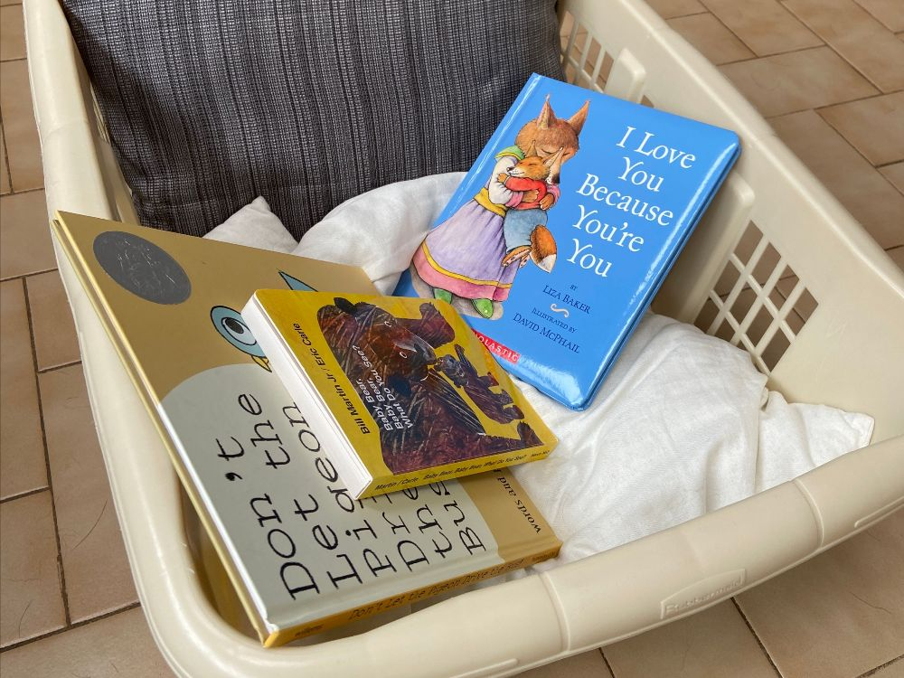 A book nook made from a laundry basket and pillows