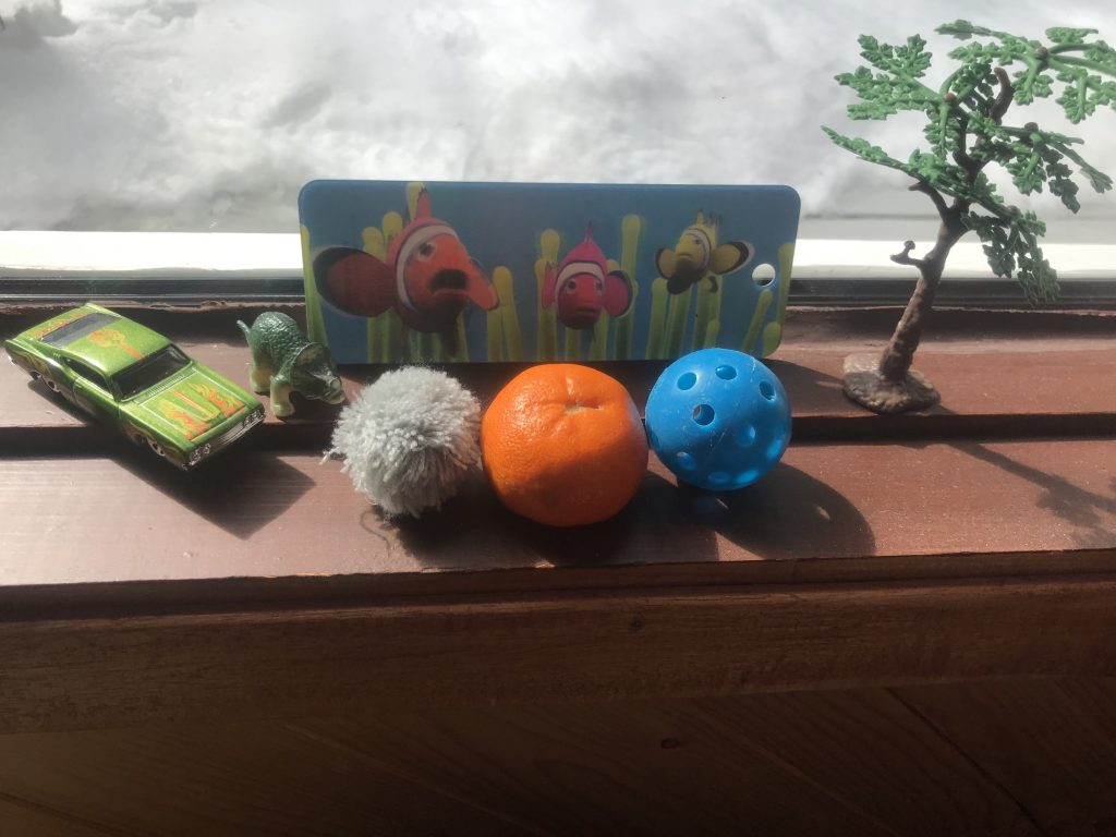 Assorted toys and objects lined up on a window sill to build a story.