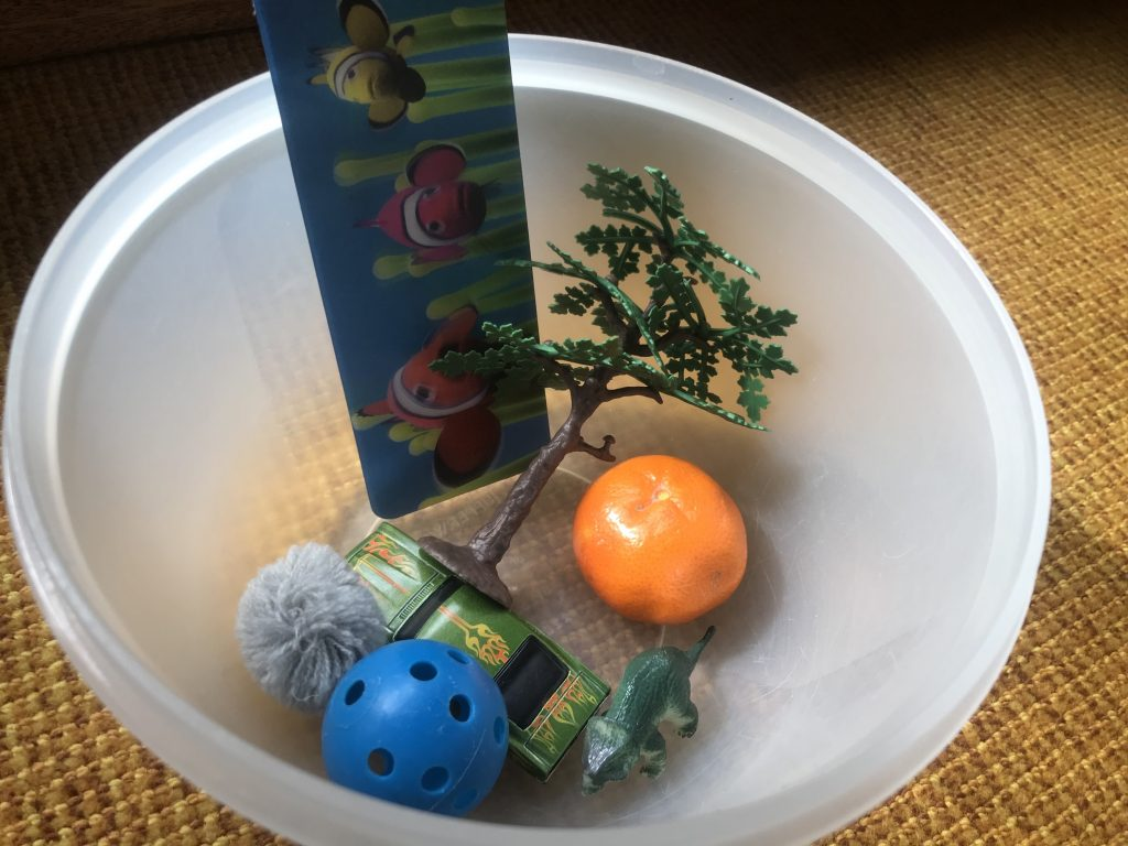 Assorted toys and objects collected in a bowl for story time.