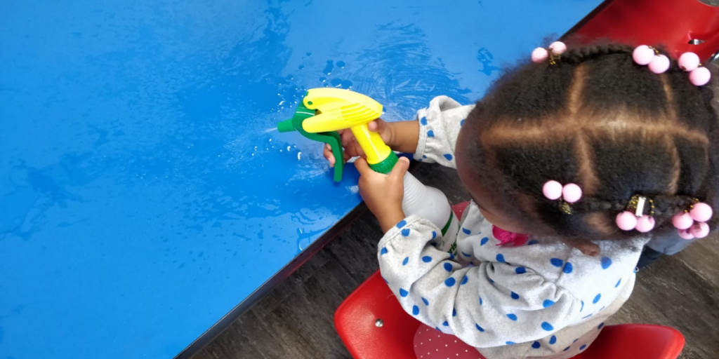 Toddler sprays water onto a table using a spray bottle.