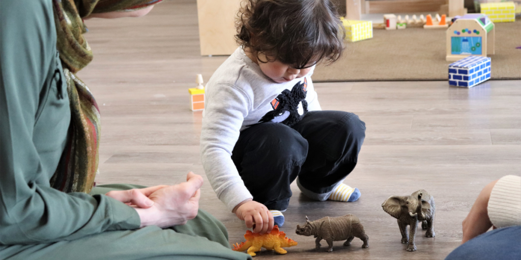 Toddler plays with toy animals.