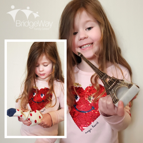 A child holds a sock with an object inside and reveals the object they have found.