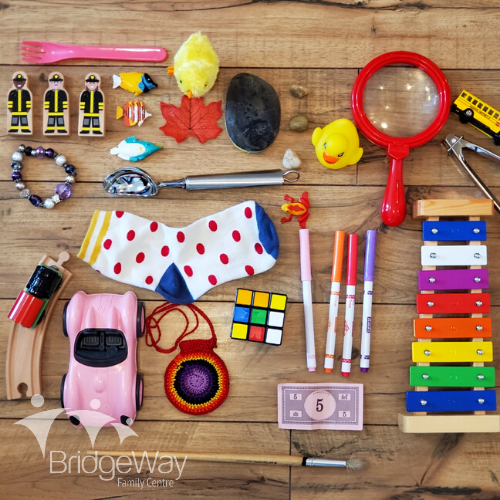 A variety of toys and objects are laid out on the floor to play I-Spy with toddlers and preschoolers.